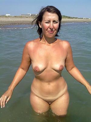 older women on rub-down the beach posing nude